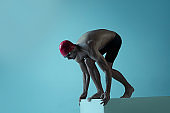 Professional male swimmer with hat and goggles in motion and action, healthy lifestyle and movement concept. Neoned style.