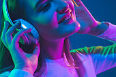 Caucasian woman's portrait isolated on blue studio background in pink-green neon light, stylish and beautiful, close up