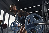 The male athlete training hard in the gym. Fitness and healthy life concept.