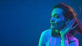 Caucasian woman's portrait isolated on blue studio background in pink-green neon light, stylish and beautiful