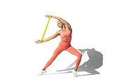 Beautiful young female athlete practicing on white studio background with shadow