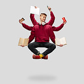 Handsome multi-armed student levitating isolated on grey studio background with equipment