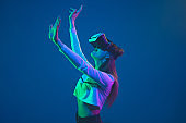 Caucasian woman's portrait isolated on blue studio background in pink-green neon light, stylish and beautiful, playing with VR-headset