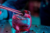 Close up of barman decorating, preparing of alcoholic cold cocktail in multicolored neon light