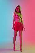 Beautiful girl in fashionable, romantic outfit on bright gradient pink-blue background in neon light