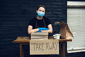 Woman preparing drinks and meals, wearing protective face mask and gloves. Contactless delivery service during quarantine coronavirus pandemic. Take away only concept.