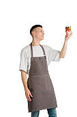 Isolated portrait of a young male caucasian barista or bartender in brown apron smiling