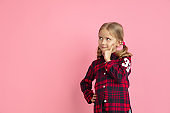 Caucasian little girl's portrait on pink studio background