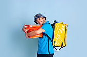 Contacless delivery service during quarantine. Man delivers food and shopping bags during insulation. Emotions of deliveryman isolated on blue background.
