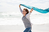 Mature woman running at beach with blue scarf