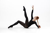 Young and graceful ballet dancer in minimal black style isolated on white studio background