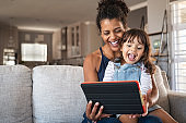 Ethnic mother and little girl having fun with digital tablet