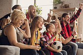 Excited, happy big family team watch football, soccer match together on the couch at home