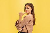 Portrait of young caucasian woman with bright emotions isolated on yellow studio background