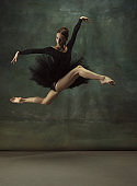 Young graceful tender ballerina on dark studio background