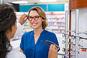 Mature woman trying new eyeglasses with optician