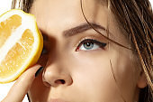 Close up of beautiful young woman with lemon slices over white background. Cosmetics and makeup, natural and eco treatment, skin care.