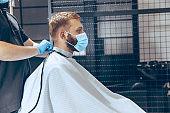 Man getting hair cut at the barbershop wearing mask during coronavirus pandemic
