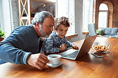 Grandfather and his grandson spending time insulated at home, stadying, watching cinema, shopping together