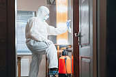 Coronavirus Pandemic. A disinfector in a protective suit and mask sprays disinfectants in the house or office