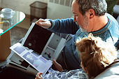 Grandfather and his grandson spending time insulated at home, having fun, reading magazine together, happy