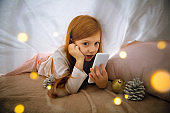Happy caucasian little girl during video call or messaging with Santa using laptop and home devices, looks delighted and happy