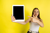 Caucasian young girl's portrait isolated on yellow studio background. Beautiful female model. Concept of human emotions, facial expression, sales, ad, youth culture.
