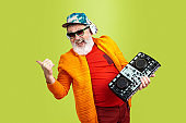 Senior hipster man wearing eyeglasses posing on green background. Tech and joyful elderly lifestyle concept