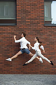 Jumping young couple in front of buildings, on the run in jump high
