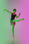 Young and graceful ballet dancer isolated on gradient pink-green studio background in neon light. Art in motion