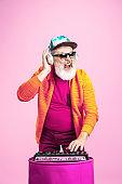 Senior hipster man wearing eyeglasses posing on pink background. Tech and joyful elderly lifestyle concept