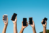 Group of hands showing smartphone with copy space