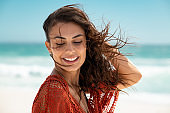 Beautiful latin woman enjoying wind at beach