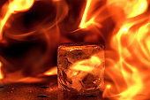 Close up big melting piece of ice on the bar counter in fireflames on it, preparation for a cocktail