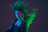 Beautiful woman's portrait with blowing hair on dark studio background in colorful neon light