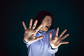 Close up portrait of young crazy scared and shocked woman isolated on dark background