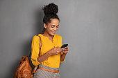 Stylish african girl using smartphone on grey wall