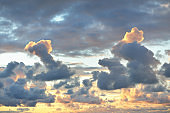 Epic sunset sky with colorful glowing clouds after thunderstorm. Golden evening sunlight. Dramatic cloudscape. Concept art, meteorology, ecology, climate change, religion, heaven, graphic resources