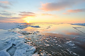 Panoramic view of the snow-covered shore of the frozen Saima lake at sunset. Ice fragments close-up. Colorful cloudscape. Symmetry reflections on the water. Finland