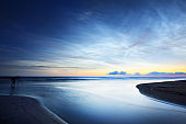 Starry sky with noctilucent clouds above the Baltic sea shore at summer solstice night. A man standing with photography equipment. Golden flowing sunlight. Long exposure. Fantastic cloudscape. Latvia