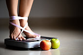 Female leg stepping on weigh scales with measuring tape and green apple. Healthy lifestyle, food and sport concept.
