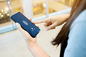Hand women holding smartphone and scan fingerprint biometric identity for unlock her mobile phone