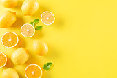 Summer composition made from oranges, lemon and green leaves on pastel yellow background. Fruit minimal concept. Flat lay, top view, copy space.