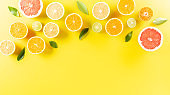 Summer composition made from oranges, lemon or lime on pastel yellow background. Fruit minimal concept. Flat lay, top view