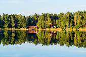 Country landscape. A view of the forest river, trees and houses in the background. Reflections on water. Latvia