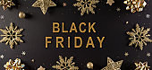 Top view of golden snowflake, stars and Christmas ball on black background. Black Friday Sale, Banner, poster composition.