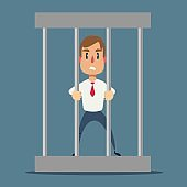 Sad businessman in office suit in prison behind the bars with metal ball chained to his leg. Financial crime concept