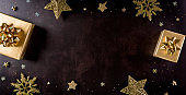 Top view of golden christmas boxes on black background with copy space for text. Black Friday Sale, Banner, poster composition.