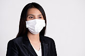 Close up of a businesswoman in a suit wearing Protective face mask and cough, get ready for Coronavirus and pm 2.5 fighting against on gray background.