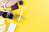 Summer holiday travel and vacation concept. Beach accessories retro film camera, sunglasses, starfish, beach hat, airplane and sea shell on yellow background.